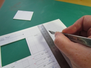 Each component of the piano is drawn out to scale on a sheet of graph paper, which is then spray-mounted on a sheet of foamed PVC. Each piece is carefully cut out with a scalpel.